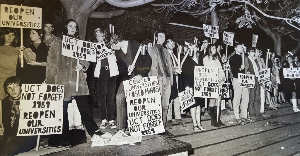 "A group of people protesting in support of academic freedom. The posters say ""Reopen our universities"", ""Closed universities, closed minds"", and ""UCT does not forget 1959""."