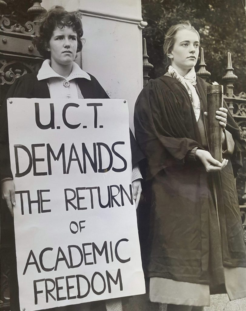 "A woman holds a placard that says ""UCT demands the return of academic freedom"" beside a woman holding a lit torch. Both are in academic dress."